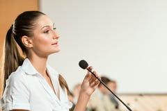 La mujer de negocios habla en un micrófono Imagenes de archivo