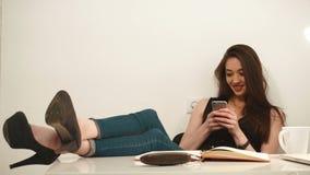 La mujer de negocios hermosa atractiva joven juega en el teléfono en oficina almacen de metraje de vídeo