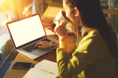 La mujer de negocios hermosa con el pelo oscuro y el suéter amarillo trabaja en coworking en café dentro usando tecnología fotografía de archivo