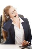 La mujer de negocios hermosa en el centro de atención telefónica está teniendo dolor trasero. Imagen de archivo libre de regalías