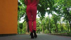 La mujer de negocios hermosa en los tacones altos y el traje rojo camina dow la calle almacen de video