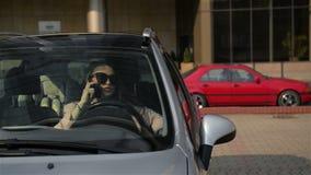 La mujer de negocios hermosa está hablando en el teléfono móvil y está sonriendo mientras que se sienta en su nuevo coche Entonce almacen de metraje de vídeo