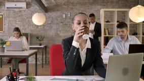 La mujer de negocios hermosa joven está mecanografiando en el ordenador portátil en la oficina, café de consumición, gente es est almacen de metraje de vídeo