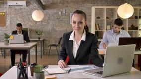 La mujer de negocios hermosa joven está mirando el ordenador portátil en oficina, mirando en la cámara, sonriendo, gente es estab almacen de video