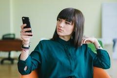 La mujer de negocios hermosa joven que se sienta en una oficina moderna en una silla y utiliza el teléfono Trabajo de la rotura Imagenes de archivo