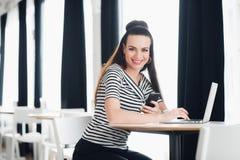 La mujer de negocios hermosa joven que trabaja en su ordenador portátil dentro, mujer adulta sonriente está utilizando un ordenad Fotos de archivo