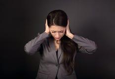 La mujer de negocios infeliz subrayada en traje gris cerró los oídos el Han Imagen de archivo