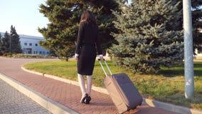 La mujer de negocios irreconocible con la maleta camina al aeropuerto para ir en viaje de negocios Señora en zapatos de los tacon almacen de video