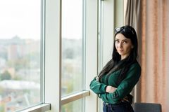 La mujer de negocios joven, acertada con el pelo negro y los brazos cruzaron está haciendo una pausa la ventana imágenes de archivo libres de regalías