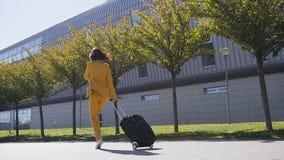 La mujer de negocios joven atractiva en un traje formal tira de una maleta, hablando en su smartphone, las prisas a un negocio metrajes
