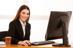 La mujer de negocios joven atractiva trabaja en su escritorio en la oficina Imagen de archivo libre de regalías
