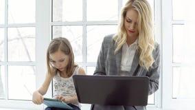 La mujer de negocios joven con el ordenador portátil y la niña se están sentando por la ventana foto de archivo libre de regalías