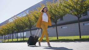 La mujer de negocios joven elegante en traje elegante tira de una maleta, hablando en su smartphone, las prisas a un negocio almacen de video