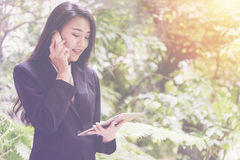 La mujer de negocios joven elegante que usa la tableta y hablando en el teléfono hace una pausa la ventana para se relaja, mirand Foto de archivo libre de regalías