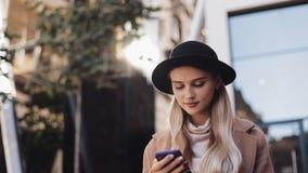 La mujer de negocios joven en capa con los soportes del sombrero cerca del centro de negocio en la ciudad, comunica vía la tablet almacen de metraje de vídeo