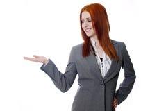 La mujer de negocios joven en el fondo blanco, distribuye, palma para arriba Fotografía de archivo