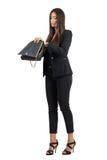 La mujer de negocios joven en el traje elegante que buscaba para algo perdió en bolso Imagenes de archivo