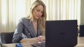 La mujer de negocios joven en traje trabaja con los documentos en el ordenador en oficina almacen de metraje de vídeo
