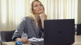 La mujer de negocios joven en traje trabaja en el ordenador en oficina almacen de video