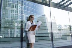 La mujer de negocios joven en vestido gris de la oficina sostiene la carpeta disponible con los documentos Situaci?n de la empres fotografía de archivo