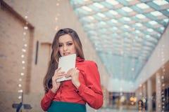 La mujer de negocios joven está en centro de la marca registrada y está presentando algo en la tableta Foto de archivo