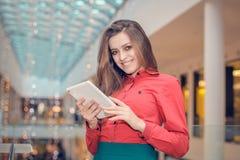La mujer de negocios joven está en centro de la marca registrada y está presentando algo en la tableta Imagen de archivo libre de regalías