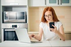 La mujer de negocios joven está utilizando un smartphone y está sonriendo mientras que trabaja en oficina fotos de archivo libres de regalías
