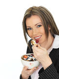 La mujer de negocios joven que come un cuenco de cereales con el yogur y sea Fotos de archivo libres de regalías