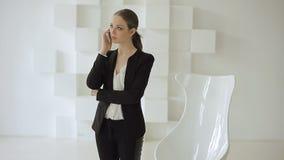 La mujer de negocios joven se coloca con un móvil cerca de una silla blanca en una oficina blanca de alta tecnología metrajes