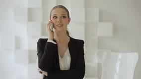 La mujer de negocios joven se coloca con un móvil cerca de una silla blanca, y sonrisas, en una oficina blanca almacen de metraje de vídeo