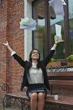 La mujer de negocios lanza para arriba documenta sentarse en un banco en un alumerzo con café Fotos de archivo libres de regalías