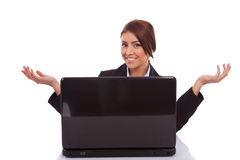La mujer de negocios le está acogiendo con satisfacción a su escritorio Fotografía de archivo libre de regalías