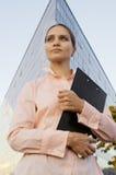 La mujer de negocios mantiene documentos la carpeta negra Fotos de archivo