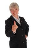 La mujer de negocios mayor manosea con los dedos para arriba Foto de archivo libre de regalías