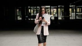 La mujer de negocios morena acertada joven está caminando a través de la ciudad con los documentos y está utilizando su Smartp metrajes