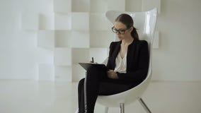 La mujer de negocios ocupada se sienta en una silla con el tablero en manos metrajes