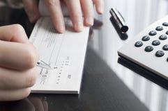 La mujer de negocios prepara la escritura de un control foto de archivo libre de regalías