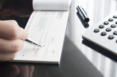 La mujer de negocios prepara la escritura de un control fotografía de archivo libre de regalías