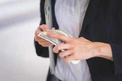 La mujer de negocios que cuenta el dinero aprovecha su mano fotos de archivo