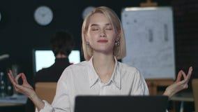La mujer de negocios que medita en yoga presenta la tabla delantera del ordenador en oficina de la noche metrajes