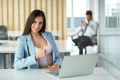 La mujer de negocios que muestra los pulgares sube gesto Hombres de negocios Foto de archivo