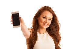 La mujer de negocios que muestra un mensaje en una pantalla de un teléfono elegante es Foto de archivo libre de regalías