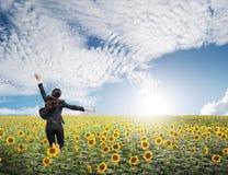 La mujer de negocios que salta en cielo azul sobre los girasoles coloca Foto de archivo
