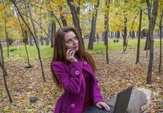 La mujer de negocios que trabaja con el ordenador portátil y el teléfono en otoño parquean La mujer tiene el pelo rojo y ojos ver Imagen de archivo