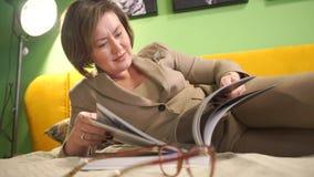 La mujer de negocios revisa la mentira de la revista almacen de metraje de vídeo