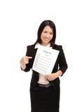 La mujer de negocios risueñamente toma el papel del item de la verificación Fotografía de archivo libre de regalías