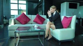 La mujer de negocios rubia cansada trabaja en la barra o el café, aplicaciones hace tabletas y llama por teléfono, café de las be almacen de video