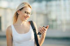 La mujer de negocios rubia lee un mensaje en el teléfono Foto de archivo