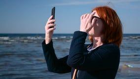 La mujer de negocios saca a su teléfono móvil el teléfono móvil del bolso en la playa almacen de metraje de vídeo