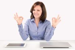 La mujer de negocios se está sentando delante de un ordenador portátil y de una tableta Imagen de archivo